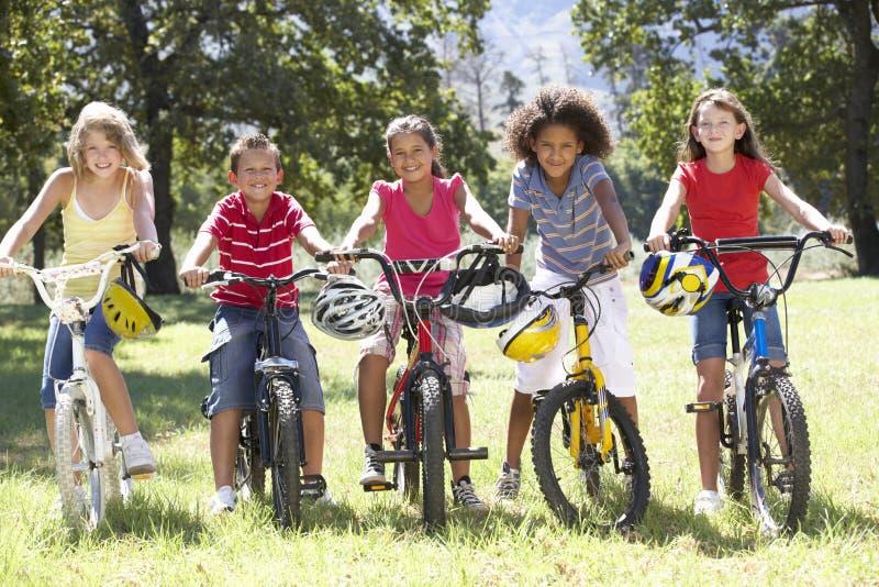 Grupp av barn som rider cyklar i bygd fotografering för bildbyråer