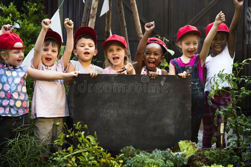 Grupp av barn som rymmer den tomma svart tavla i trädgård royaltyfria bilder