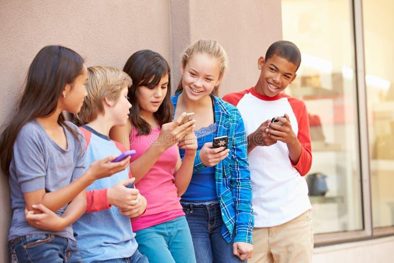 Grupp av barn som sitter i galleria genom att använda mobiltelefoner arkivfoton