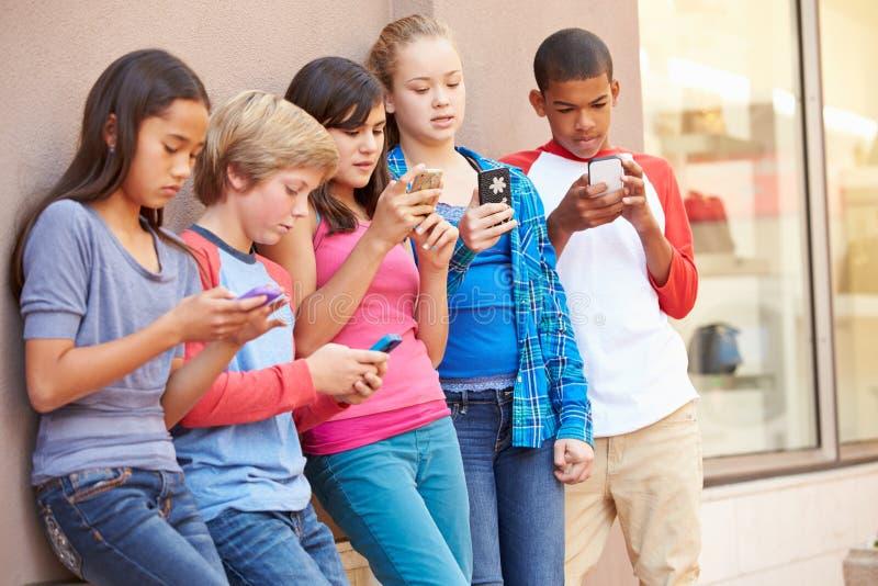 Grupp av barn som sitter i galleria genom att använda mobiltelefoner royaltyfri fotografi