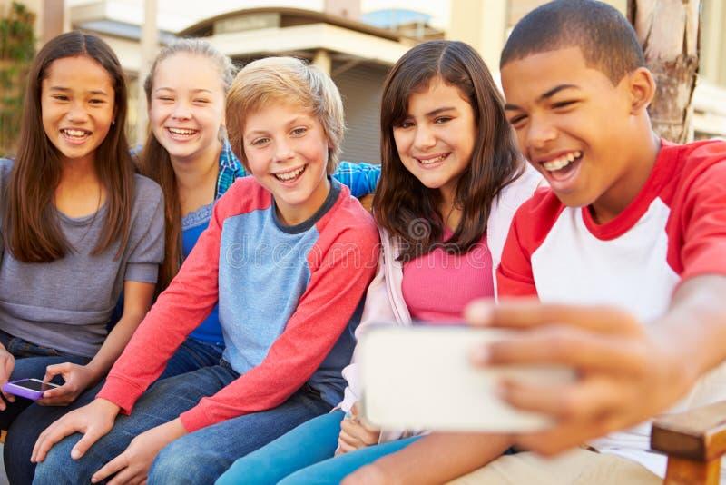 Grupp av barn som sitter på bänk i gallerian som tar Selfie arkivfoto