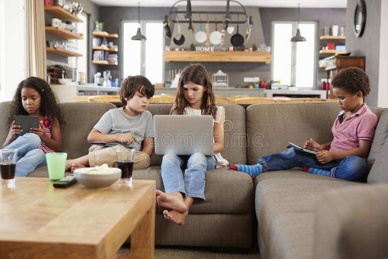 Grupp av barn som sitter på Sofa Using Digital Devices royaltyfri foto