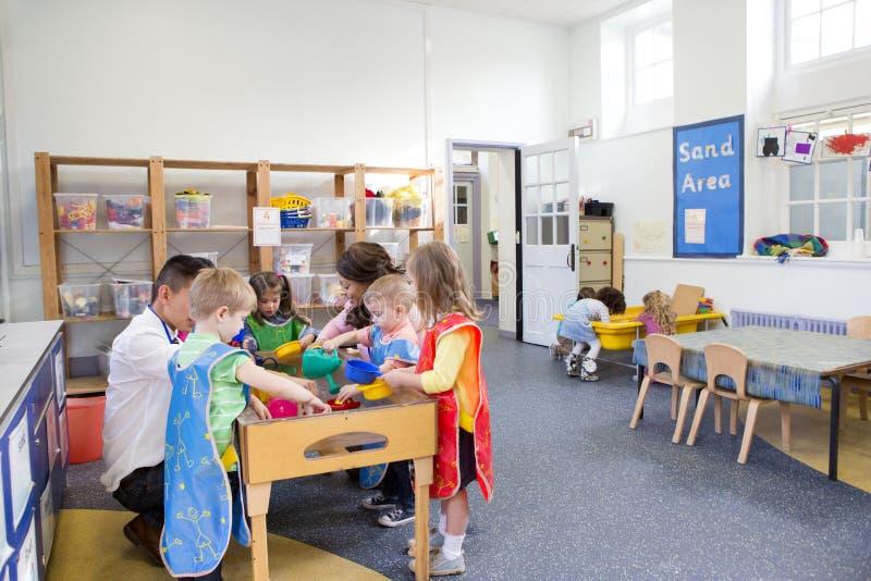 Grupp av barn som spelar i ett klassrum royaltyfria foton