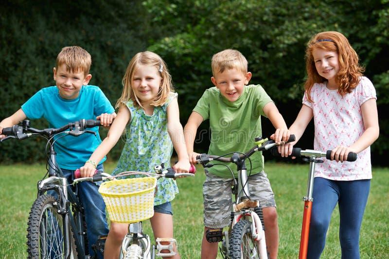 Grupp av barn som spelar på cyklar och sparkcykeln royaltyfri foto