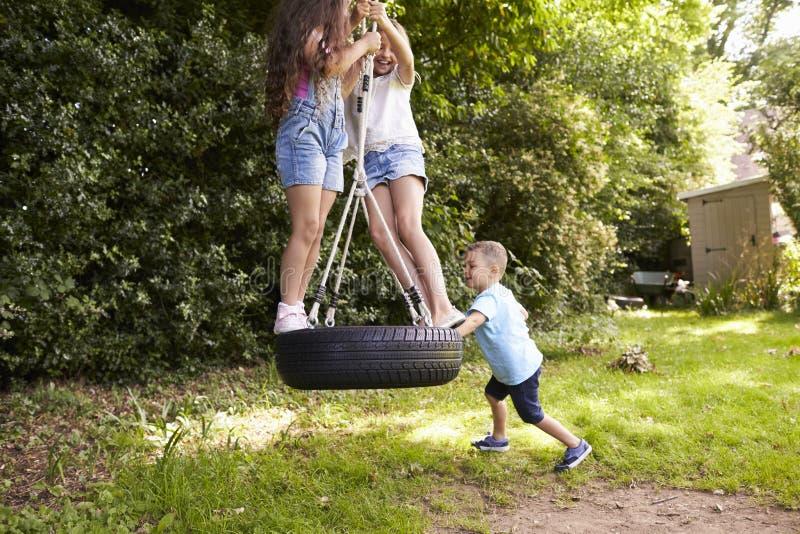 Grupp av barn som spelar på gummihjulgunga i trädgård royaltyfri fotografi