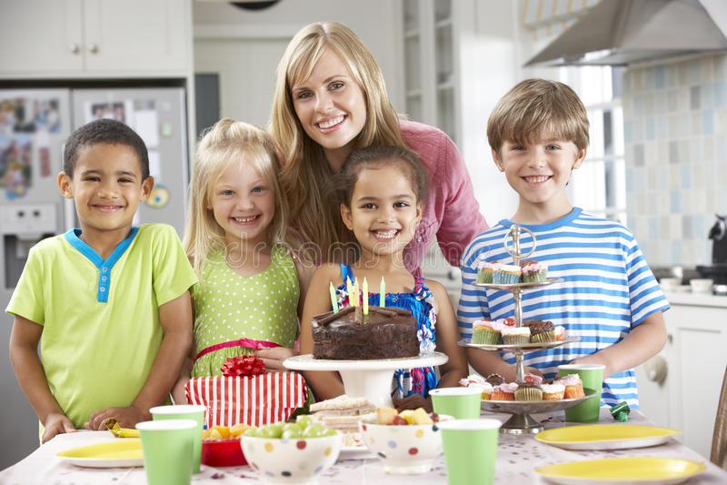 Grupp av barn som står med modern vid tabellen som läggas med mat för födelsedagparti royaltyfria foton