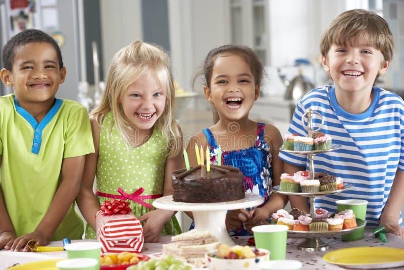 Grupp av barn som står vid tabellen som läggas med mat för födelsedagparti royaltyfri fotografi