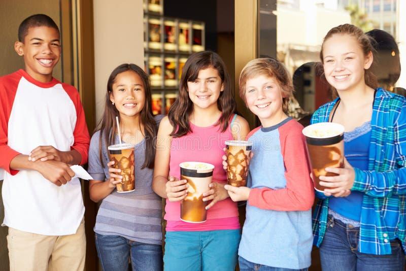 Grupp av barn som tillsammans står utanför bio royaltyfri foto