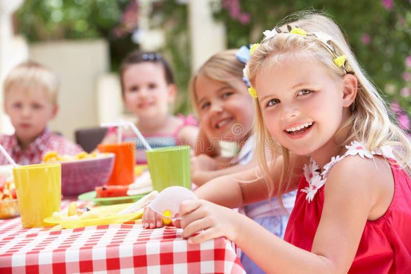 Grupp av barn som tycker om den utomhus- Teadeltagaren arkivfoto