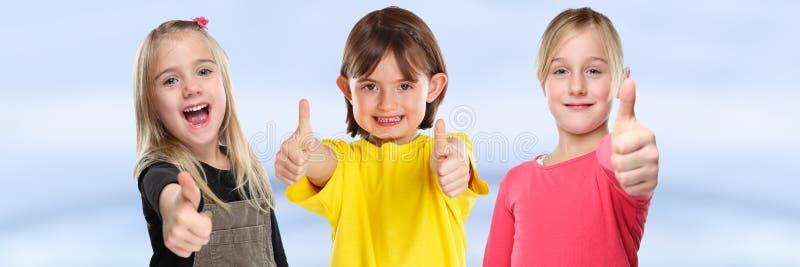 Grupp av barnungar som ler unga liten flickaframgångtummar upp positivt baner royaltyfri fotografi