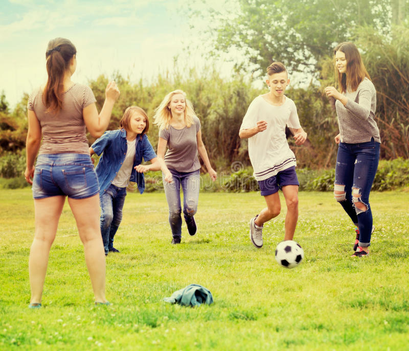 Grupp av bekymmerslösa tonåringar som sparkar fotboll arkivfoton