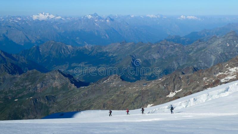 Grupp av bergsbestigare som stiger ned på glaciären fotografering för bildbyråer