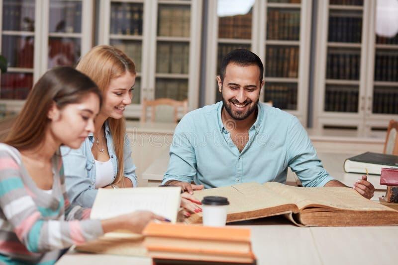 Grupp av blandras- folk som studerar med böcker i högskolaarkiv royaltyfri fotografi