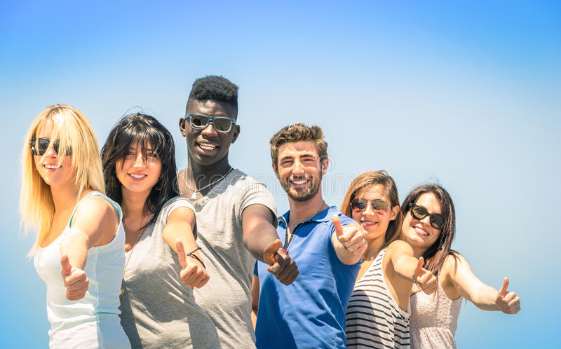 Grupp av blandras- lyckliga vänner med tummar upp royaltyfria foton