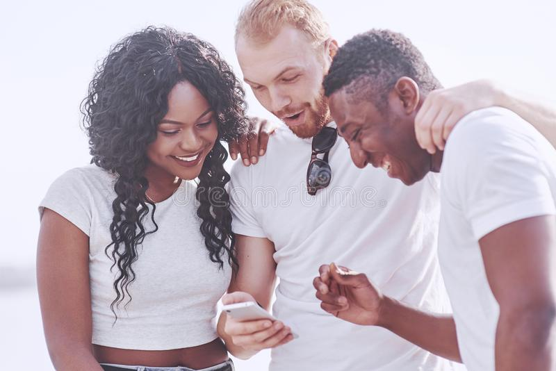 Grupp av blandras- lyckliga vänner som utomhus använder grejen Begrepp av alla lycka och mång- etniskt kamratskap tillsammans royaltyfri bild