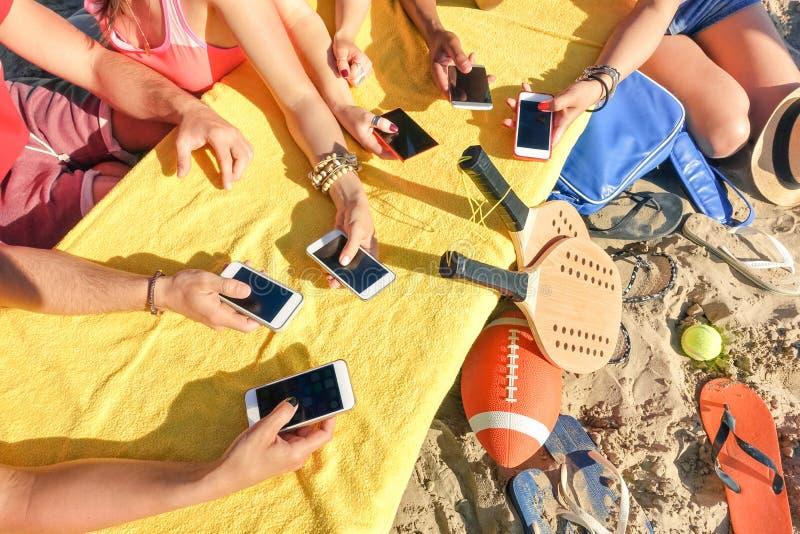 Grupp av blandras- vänner som har gyckel samman med smartphonen royaltyfri foto