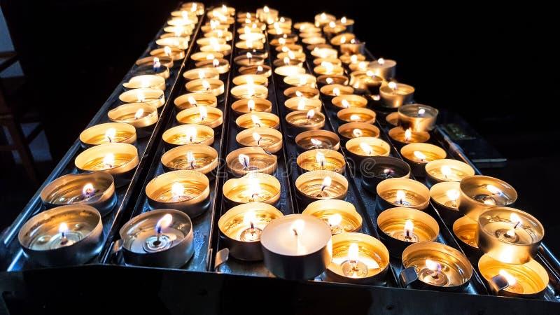 Grupp av brännande stearinljus för skinande brand på en metallhållare royaltyfri fotografi