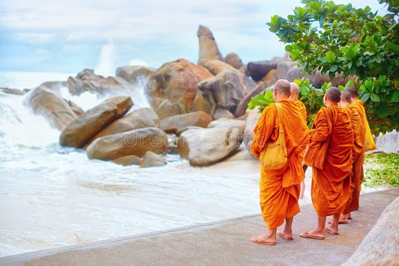 Grupp av buddistiska munkar som håller ögonen på stormen på den steniga stranden royaltyfri foto