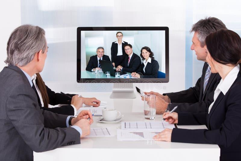Grupp av businesspeople i videokonferens arkivfoto