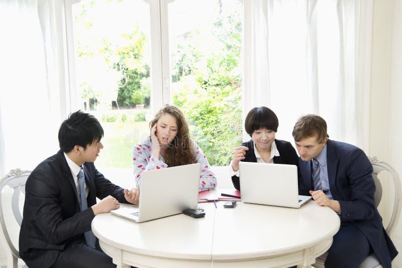 Grupp av businesspeople som arbetar på bärbara datorn royaltyfria bilder
