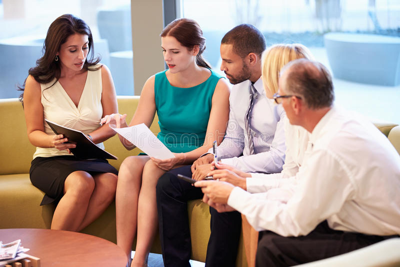 Grupp av Businesspeople som har möte i regeringsställning av lobbyen royaltyfri fotografi