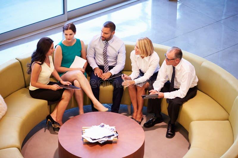 Grupp av Businesspeople som har möte i regeringsställning av lobbyen fotografering för bildbyråer