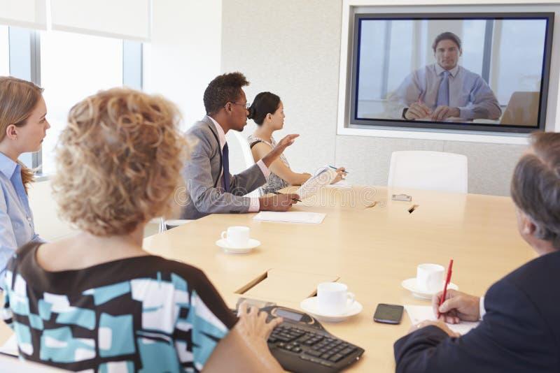 Grupp av Businesspeople som har videokonferens i styrelse royaltyfria foton