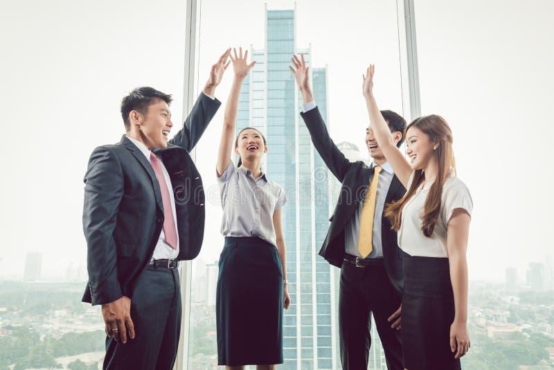Grupp av businesspeople som lyfter deras händer royaltyfri bild
