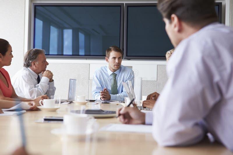 Grupp av Businesspeople som möter runt om styrelsetabellen arkivbilder
