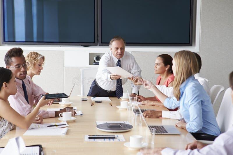 Grupp av Businesspeople som möter runt om styrelsetabellen royaltyfri fotografi