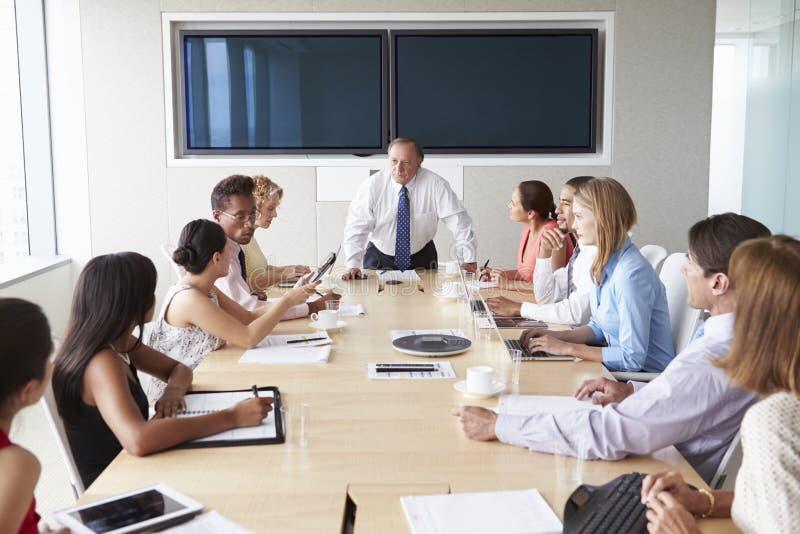 Grupp av Businesspeople som möter runt om styrelsetabellen arkivbild
