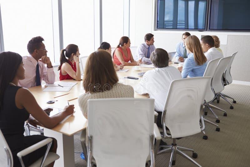 Grupp av Businesspeople som möter runt om styrelsetabellen fotografering för bildbyråer