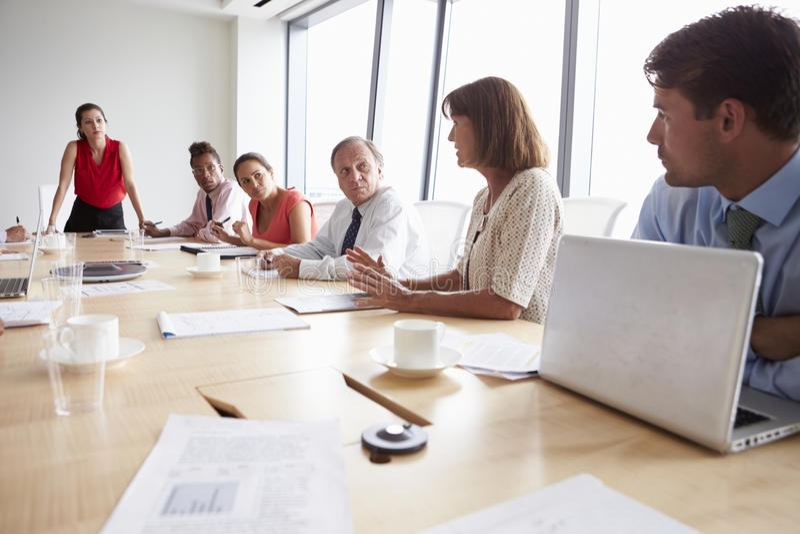 Grupp av Businesspeople som möter runt om styrelsetabellen royaltyfria bilder
