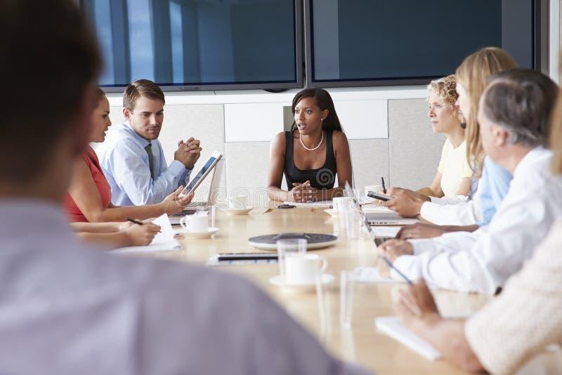 Grupp av Businesspeople som möter runt om styrelsetabellen royaltyfri bild