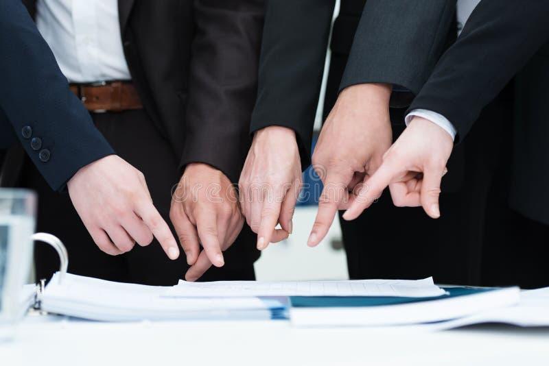 Grupp Av Businesspeople Som Pekar Till Ett Dokument Arkivbilder
