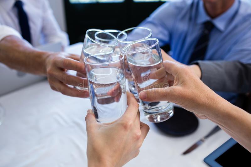 Grupp av businesspeople som rostar exponeringsglas av vatten i restaurang arkivbild
