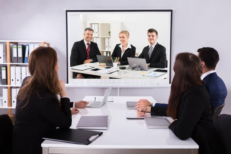 Grupp av Businesspeople som ser projektorn royaltyfri fotografi