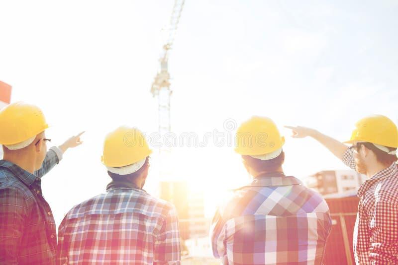 Grupp av byggmästare i hardhats på konstruktionsplatsen royaltyfri foto