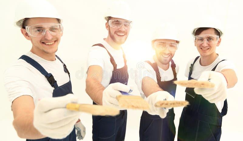 Grupp av byggnadsarbetare Isolerat på vit royaltyfria foton