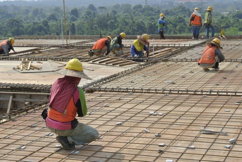 Grupp av byggnadsarbetare som fabricerar stången och formwork för förstärkning för golvtjock skiva arkivbild