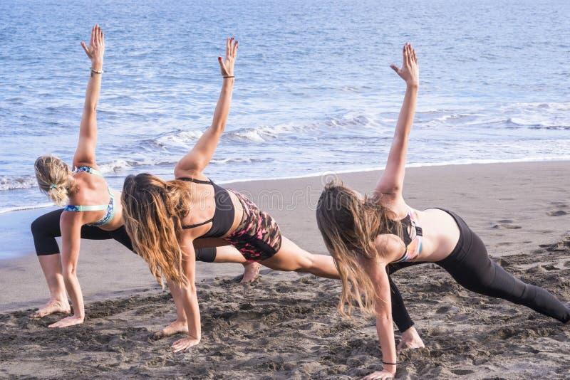 Grupp av caucasian attraktiva flickawoind?vningar och pilates p? kusten p? havet semester och sunt g?ra f?r livsstil royaltyfri bild