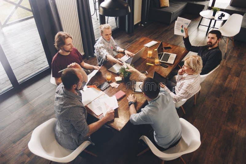 Grupp av coworking folk som sitter runt om trätabellen och workin arkivbild