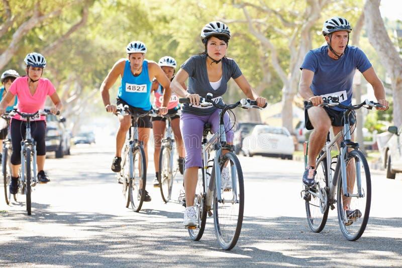 Grupp av cyklister på den förorts- gatan royaltyfri fotografi