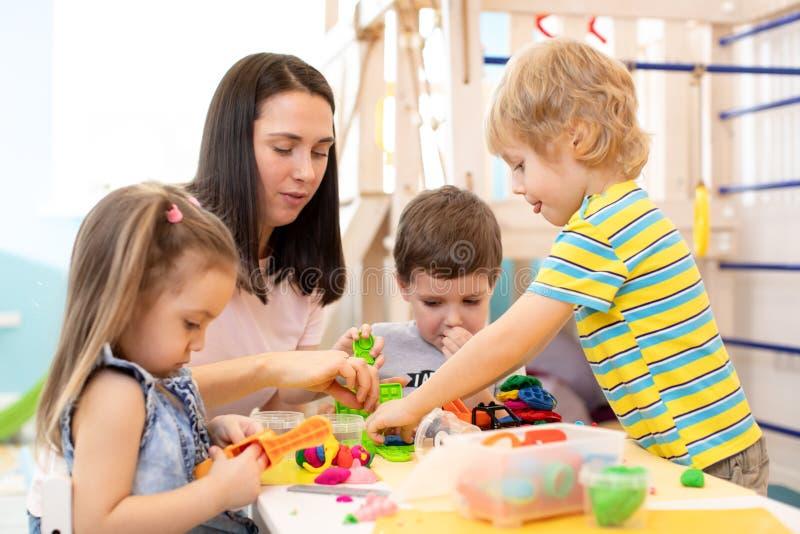 Grupp av dagisbarn som spelar med plasticine eller deg Små ungar har en gyckel samman med färgrikt modellera arkivfoto
