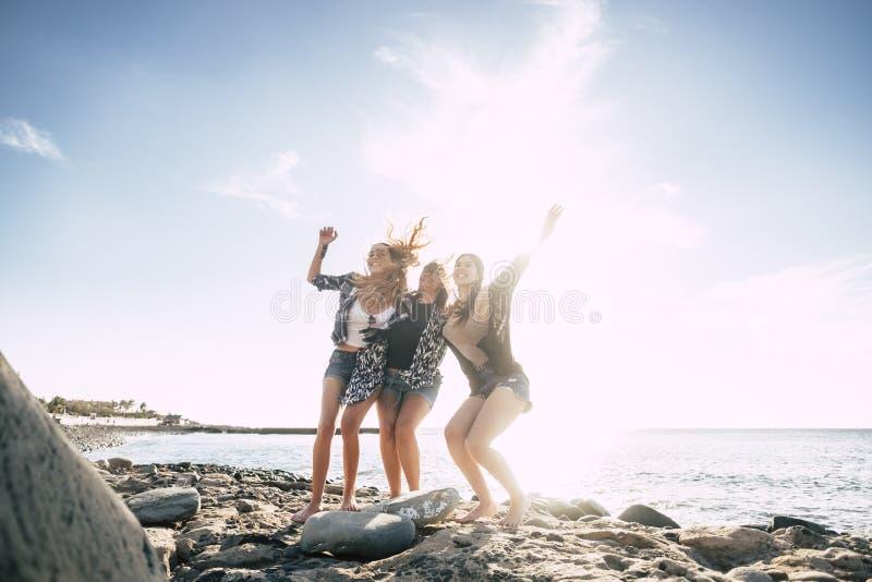 Grupp av dansen för ung kvinna tre på stranden arkivfoto