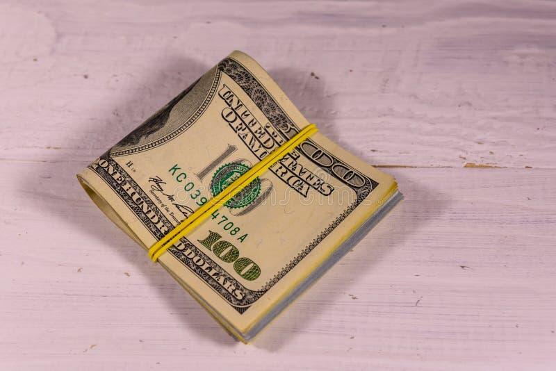 Grupp av de hundra dollarräkningarna med gummi på trätabl royaltyfri bild
