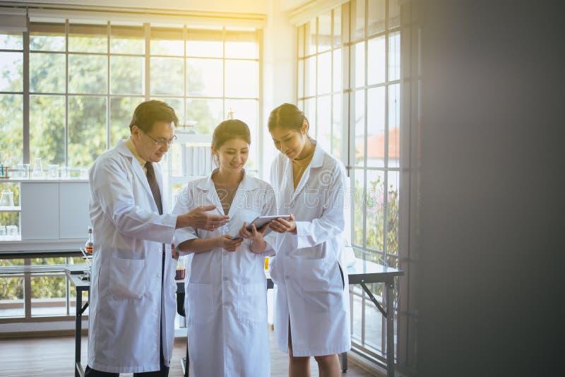 Grupp av den asiatiska forskaren som använder minnestavladatoren och tillsammans analyserar information om dataforskning i labora arkivbilder