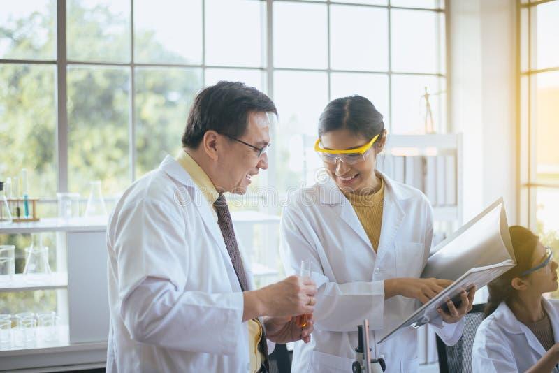 Grupp av den asiatiska forskaren som tillsammans arbetar och analyserar information om dataforskning i det laboratary arkivbild