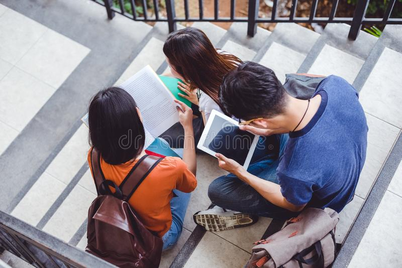 Grupp av den asiatiska högskolestudenten som ut använder minnestavlan och mobiltelefonen arkivbild