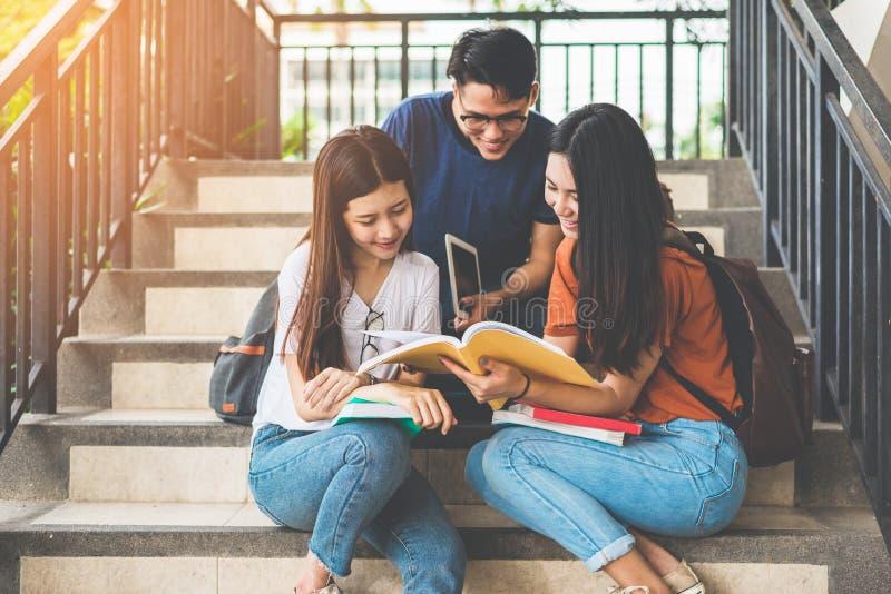Grupp av den asiatiska h?gskolestudenten som anv?nder minnestavlan och mobiltelefonen utanf?r klassrum Lycka och utbildning som l royaltyfria bilder
